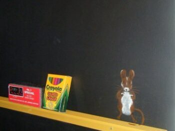Stenciled mouse on blackboard wall